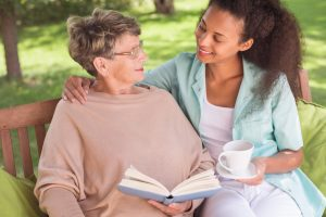 senior care Phoenix AZ caregiver holding a cup of tea for senior woman holding a book