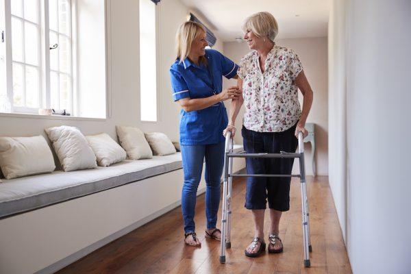Nurse helping senior woman use a walking frame