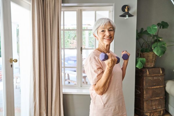 Portrait of a smiling senior woman lifting dumbbells during a workout session in her living room at home
