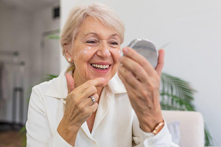 senior lady applying moisturizer to face